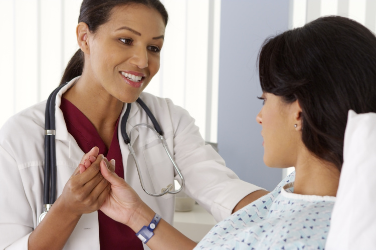 Female doctor holding Hispanic woman's hand and talking